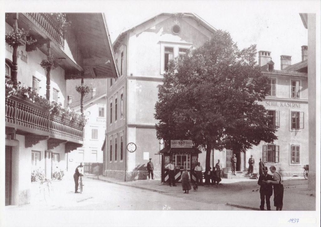 Wörgl in den 1930er Jahren: Links das Marktgemeindeamt, hinter der Kaiser-Linde das alte Volksschul-Gebäude, das ab 1934 als Kaserne benützt wurde. Auch die Trafik - das Häuschen unter der Linde - nahm damals Freigeld an. L Foto: Unterguggenberger Institut Archiv