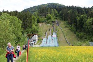 Blick aufs Wörgler Sprungschanzen-Gelände: Die 1932 mit Wörgler Freigeld gebaute große Sprungschanze (Schneise im Wald rechts) wurde nach dem Umbau des Schanzengeländes nicht mehr aktiviert – sie entspricht nicht mehr dem heute geforderten Schanzenprofil.